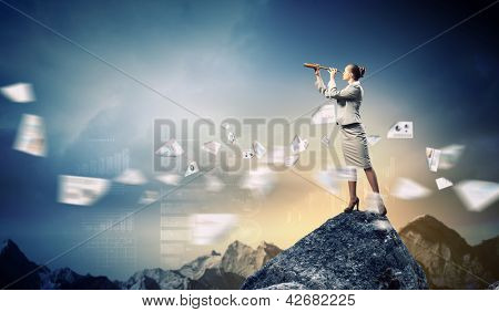 Image of businesswoman looking in telescope standing a top of rock