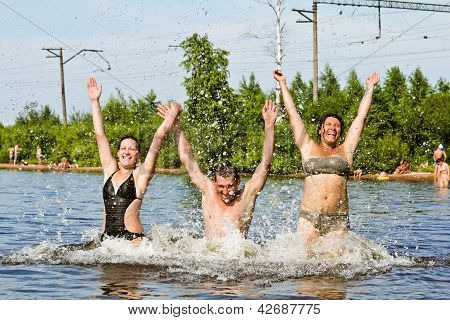 Young People Jump And Splash Around In The Lake