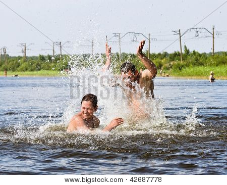 A Guy And A Girl Enjoy Splashing Around In The Lake