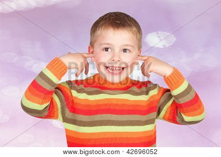 Funny child covering his ears isolated on a pink background