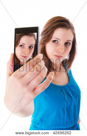 Young girl taking a self portrait with her phone, isolated over white