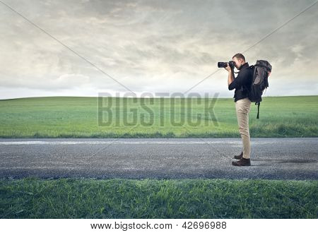 photographer with professional camera on desert road