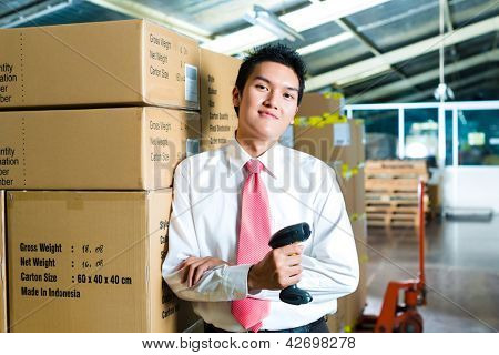 Young man in a suit with a bar code scanner in a warehouse