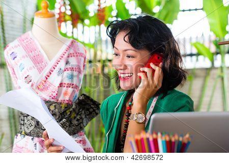 Freelancer - mode-ontwerper werkt thuis aan een ontwerp of ontwerp, ze maakt gebruik van een mobiele telefoon, om te praten