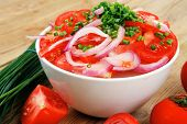 healthy food : fresh tomato salad in white bowl with bunch of chives and raw tomatoes on twig , onio
