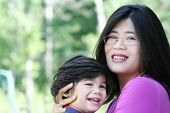 stock photo of biracial  - Asian mother lovingly holding her disabled son outdoors in summer - JPG