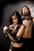 stock photo of sado-masochism  - Pretty woman in leather clothing is holding a wired slave - JPG