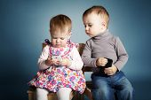 stock photo of peep  - little boy and girl playing with mobile phones - JPG