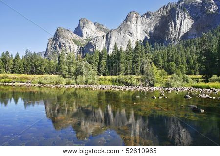 Phenomenally scenic Yosemite Valley. The mirror surface of the Merced river reflects the picturesque cliff tops and blue sky