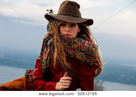 young blond woman in autumn fashion clothes,  red leather jacket, hat, cashmere scarf and brown skirt outdoor shot