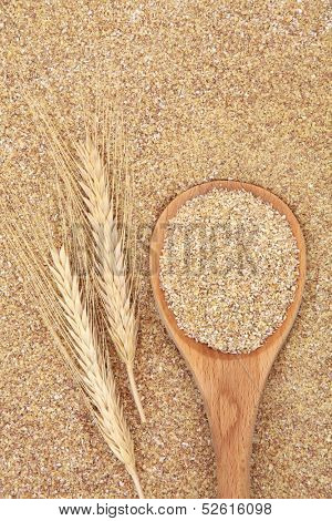 Wheatgerm in a wooden spoon with wheat ears forming a textured background.