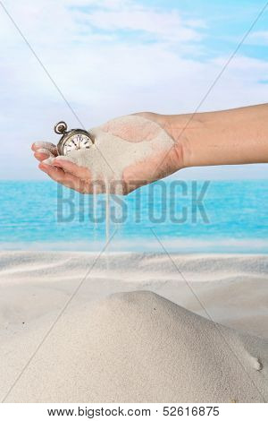 Hand with pocket watch and sand flowing on the beach