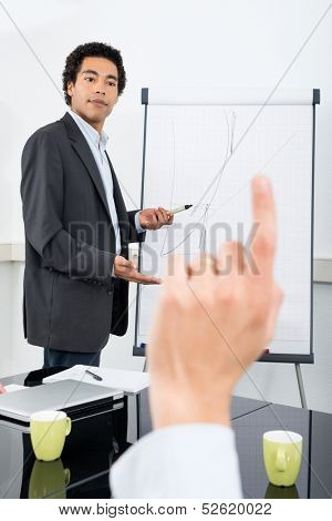 Businessman explaining graph on filpchart with colleague raising hand in conference room