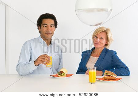 Two coworkers during lunch at a counter in their office, with fresh orange juice and healthy sandwiches