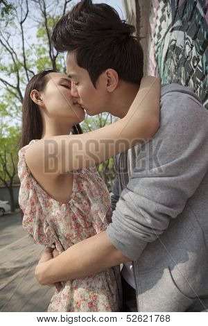 Young couple with arms around each other kissing by a wall with graffiti