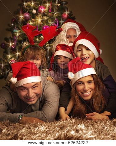 Closeup portrait of big happy family with Santa Claus lying down near Christmas tree, holiday celebration, joy and happiness concept