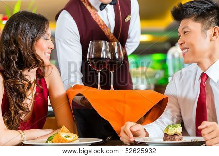 Asian Chinese waiter or steward serving man and woman or couple red wine in glasses on a tray in fancy restaurant or hotel
