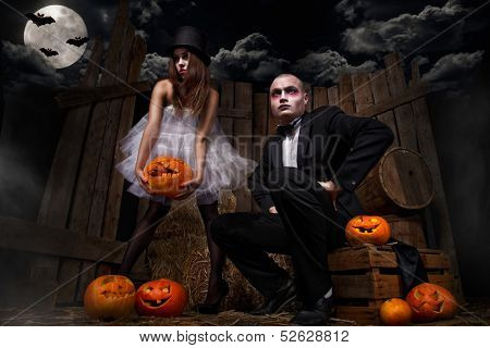 Portrait of a man and sexy woman vampires with halloween pumpkin against wooden background.
