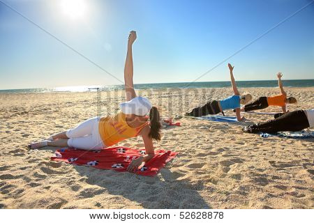 Women doing yoga exercise  Salamba Kapotasana or Supported Pigeon Pose on an empty beach