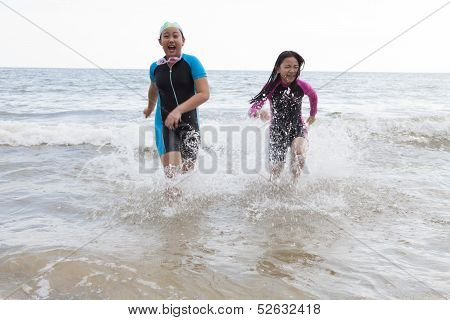 Two Girl Wearing Wet Suit  Playing On Sea Beach With Happiness Emotion