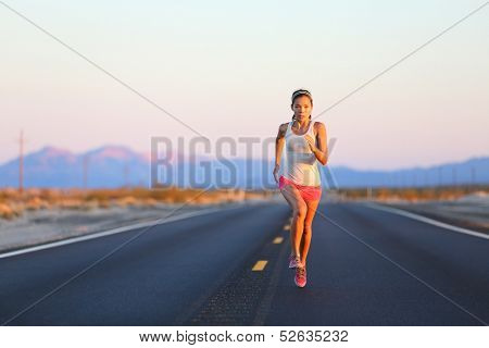 Running woman sprinting on road highway at sunset at countryside in USA. Fit female fitness girl training outdoor in beautiful landscape. Multiracial Caucasian Asian female runner in her 20s.