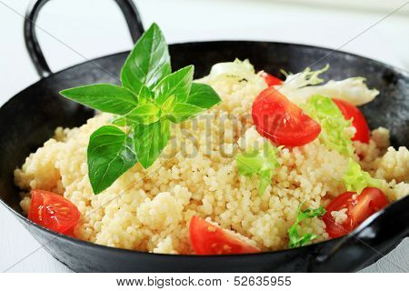 couscous with cherry tomatoes and lettuce served in a pan