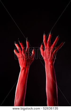 Red demonic hands with black nails, Halloween theme, studio shot on black background
