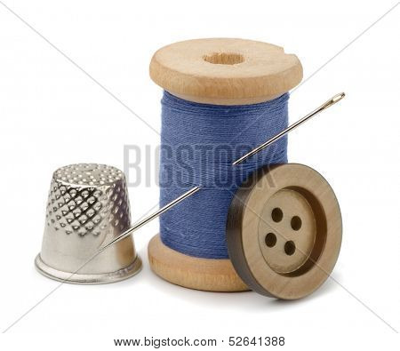 Spool of blue thread, needle, button  and thimble isolated on white