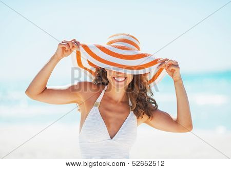 Portrait Of Smiling Young Woman In Swimsuit Hiding Behind Beach Hat