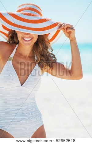 Portrait Of Happy Young Woman In Swimsuit Hiding Behind Beach Ha