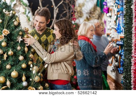 Happy young couple looking at Christmas tree with parents shopping in background at store