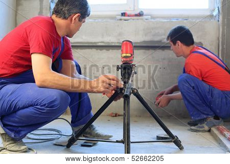 Two workers makes measurements with laser level tool in a niche for radiators in apartment with a rough finish