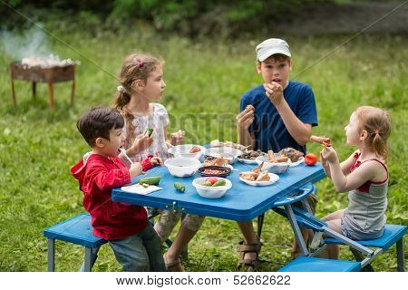 Four children eat meat with vegetables at the picnic on pembroke table, boy on the left in focus