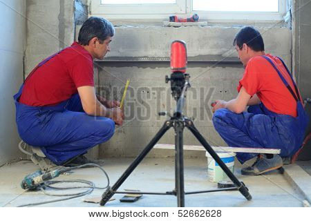 Two workers makes measurements with laser level tool in a niche for radiators in new apartment