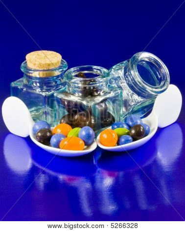 Crystal Bottles And White Spoons With Chocolate Of Colors