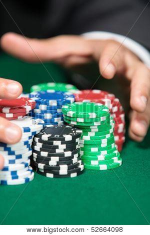 Poker player raking a big pile of chips. Risky entertainment of gambling