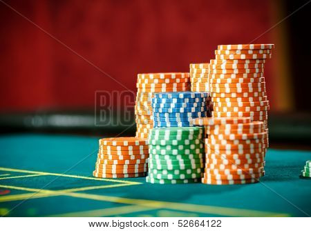Close up shot of piles of chips on the roulette table. Symbol of addiction to the gambling