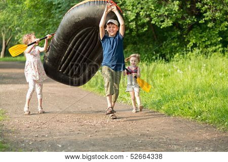 Three happy children carry a rubber boat with oars on a footpath in the forest