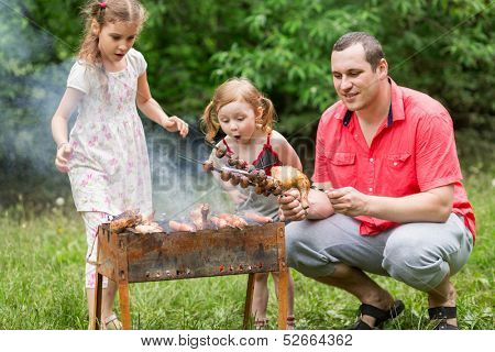 A family of three making barbecue on the grill on nature, little girl blowing on a skewer with mushrooms.