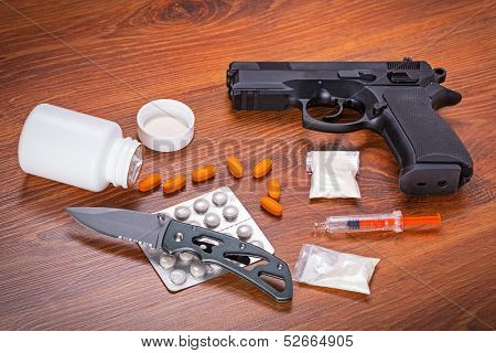 Set of narcotics and handgun on wooden table