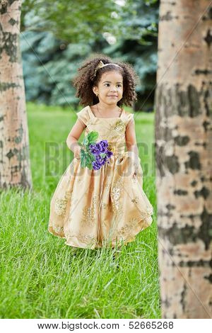 Little mulatto girl in beige party frock stands between trees in park