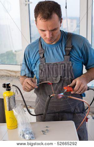 Worker welds copper tube oxyfuel gas welding