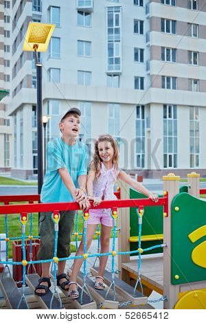 Boy and his younger sister play on children playground in house yard