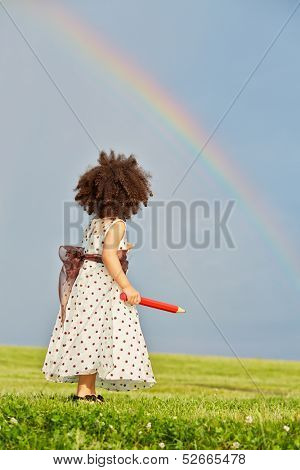 Little girl  dressed in polka-dot gown stands on meadow holding big red pencil in her hand and look at rainbow in the sky