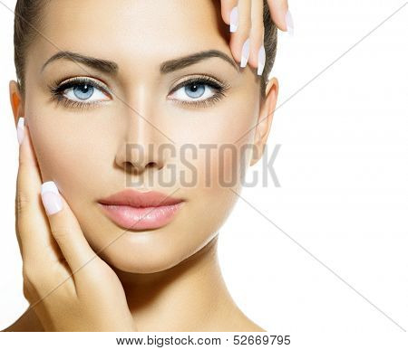 Beautiful Girl Touching her Face. Beauty Spa Woman Portrait. Perfect Fresh Skin. Pure Beauty Model Girl. Youth and Skin Care Concept. Isolated on White Background. Looking at Camera
