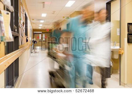 Blurred motion of doctor and nurse pulling stretcher in hospital