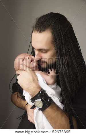 The Young Father Embraces The Baby