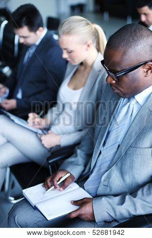 Image of business people sitting in rows and making notes at conference