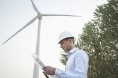 pic of button down shirt  - Young engineer in a hardhat looking down at a blueprint in front of a wind turbine - JPG