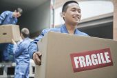 stock photo of moving van  - Movers unloading a moving van and carrying a fragile box - JPG
